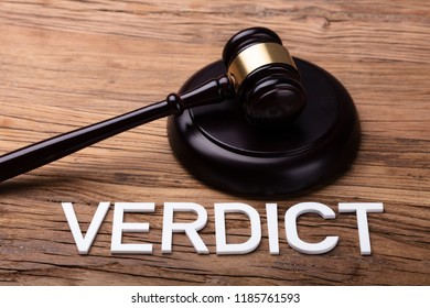 Verdict Text In Front Of Brown Gavel On Wooden Table