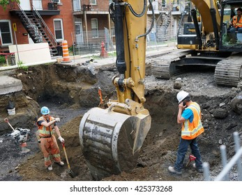 Verdun , Quebec, Canada May 19 2016 - road crew heavy machinery working at Rue Gordon digging up concrete and dirt for drainage sewer pipes and pavement repair