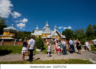 VERKHOVYNA, UKRAINE - AUG 15: People in formal attire go out of the village Orthodox church on August 15, 2014. Verkhovyna with pop. 5,500  is located in the Hutsul region of the Carpathian Mountains