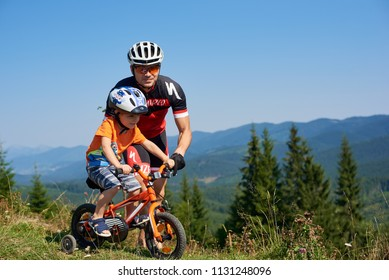 Verkhovyna, Ukraine - August 19, 2017: Young athletic father in biker outfit teaches small preschool boy to ride a bike on grassy mountain hill. Parenthood, traveling and family recreation concept.