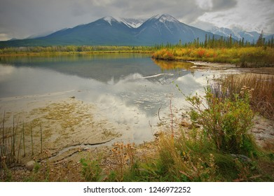 Vermilion Lakes (Canada): mountains  (Sundance Range) reflected on the water in the background, trees in autumn colours and storm clouds