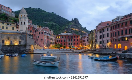 Vernazza in Cinque Terre Italy and its harbor during the early evening with boats rocking and clouds on the horizon.