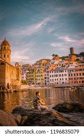 Vernazza harbor Cinque terre Italy during sunset , man at an rock cliff looking sunset Vernazza
