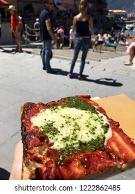 VERNAZZA, ITALY AUGUST 12TH, 2018 - Slice of Italian pizza with mozzarella cheese and pesto, a recipe particular to the Liguria region. Tourists and visitors to Vernazza in the background.