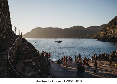 Vernazza, Italy - October 30, 2016: People waiting for a tour boat in Vernazza, one of Cinque Terre villages, at sunset. Cinque Terre was included as a UNESCO World Heritage Site in 1997.