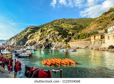 Vernazza, Italy - September 22 2017: Tourists walk the old pier past boats and life jackets at the small harbor of the coastal village of Vernazza Italy, part of the Cinque Terre