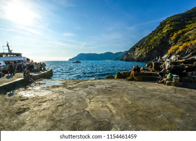 Vernazza, Italy - September 23 2017: Tourists wait in in the late afternoon sun while boarding a tour boat along the Ligurian Coast of Italy at the Cinque Terre village of Vernazza, Italy