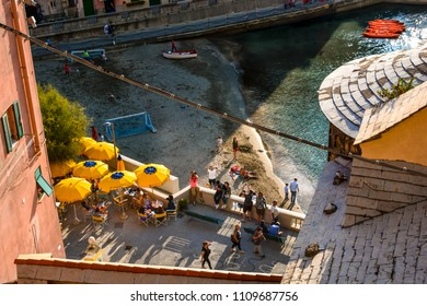 Vernazza, Italy - September 24 2017: Small sandy beach and harbour of the Cinque Terre Italy village of Vernazza, late afternoon with local children playing football and tourists dining