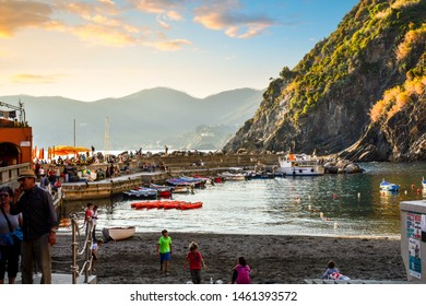 Vernazza, Italy - September 26 2018: Local Italian children play football on the sandy beach at  the Vernazza, Italy harbor as tourists watch at dusk along the Cinque Terre coast of the Ligurian sea