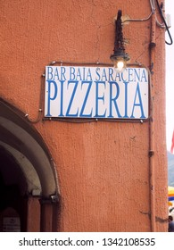 VERNAZZA, ITALY-SEPTEMBER: A pizzeria pizza restaurant sign is seen on old plaster building in Vernazza, Cinque Terre, Italy in September 2018.