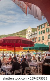 Vernazza, Liguria / Italy - April 22 2019: View of the square of the Cinque Terre's fishing village, Unesco Site since 1997, crowded with tourists walking and sitting at outdoor café and restaurant