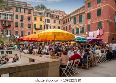 Vernazza, Liguria / Italy - April 22 2019: Scenic view of the square of the Cinque Terre fishing village Unesco Site crowded with tourists eating under the sun umbrellas in outdoor café and restaurant