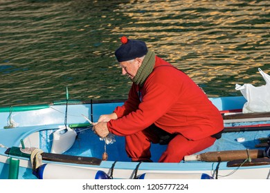 VERNAZZA, LIGURIA, ITALY - JANUARY 2, 2015: An elderly fisherman in the port of Vernazza on a rowing boat. Cinque terre national park in Liguria Italy
