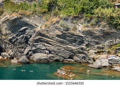 VERNAZZA, LIGURIA, ITALY - JULY 22, 2019: cliff and Mediterranean sea, Vernazza village. People swim or sunbathe. Cinque Terre, UNESCO world heritage site. Vernazza, La Spezia, Liguria, Italy, Europe