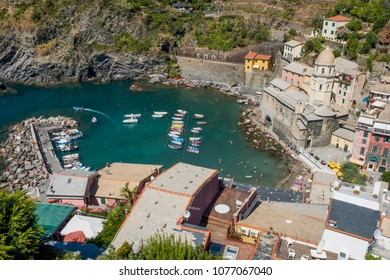 Vernazza port and beach seen from the castle tower with boats leaving the bay and tourist on the beach