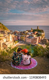 Vernazza village, aerial view on sunset, Seascape in Five lands, Cinque Terre National Park, Liguria Italy Europe, couple on picnik blanket watching sunset over Vernazza