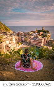 Vernazza village, aerial view on sunset, Seascape in Five lands, Cinque Terre National Park, Liguria Italy Europe, young man on picnic blanket watching sunset Vernazza