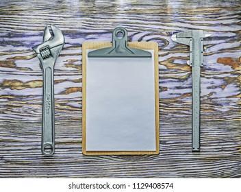 Vernier caliper adjustable spanner clipboard on wooden board.
