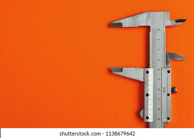 Vernier caliper of gray color on orange table with copy space for your text