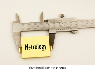 A vernier caliper and yellow note with word metrology