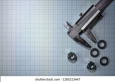 Vernier calliper, nuts and shims over graph paper background