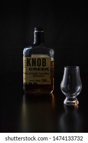 Vero Beach, Florida; USA; July 30, 2019. A glencairn whiskey glass is sitting off center to a bottle of 100 proof kentucky straight bourbon. There is a black reflective background.