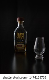 Vero Beach, Florida; USA; July 30, 2019. A glencairn whiskey glass is sitting off center to a small bottle of bourbon. There is a black reflective background.