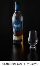 Vero Beach, Florida; USA; July 30, 2019. A glencairn whiskey glass accompanied by a delicious bottle of scotch on a reflective black service.