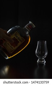 Vero Beach, Florida; USA; July 30, 2019. Pouring a glencairn glass of Kentucky straight bourbon whiskey in front of a black background. The glass reflections shine off the black wood surface.