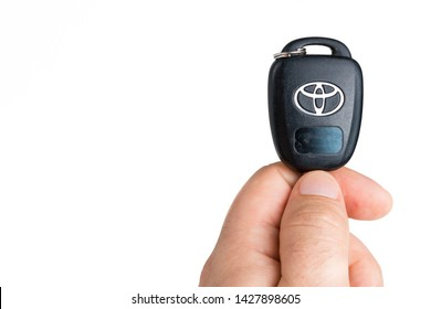 Vero Beach, Florida; USA; June 14, 2019.       A male is holding onto a Toyota car key with the Toyota logo completely visible. The plastic key handle is sticking up out of the males hand. The backgro