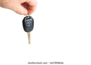 Vero Beach, Florida; USA; June 14, 2019.        A male is dangling a Toyota car key with the locking buttons visible. Only the fingers of the males hand are visible. The background is white.