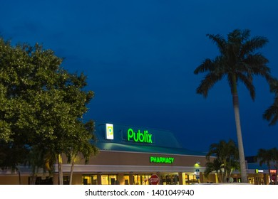 Vero Beach, Florida; USA; May 11, 2019.    A Publix storefront image taken during twilight hours as seen from the parking lot. The neon signs are lit from the rooftop. The store has palm trees that fr