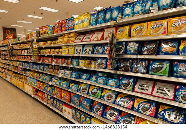 Vero Beach, FL/USA - 8/2/19 - The cookie aisle in a grocery store with two people shopping.