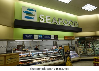 Vero Beach, FL/USA - 8/2/19 - The seafood  department in a grocery store with an employee behind the counter.