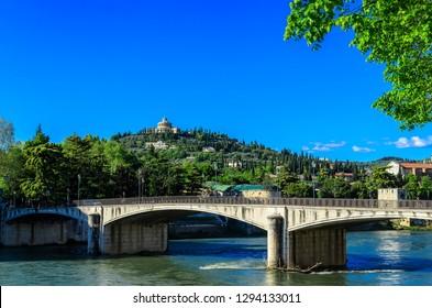 Verona Adige River Embankment view of the Garibaldi Bridge (Ponte Garibaldi) and the Sanctuary of the Madonna of Lourdes (Santuario della Madonna di Lourdes)