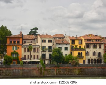 Verona, Italy - 6/8/2018: Colorful ancient houses along the Adige River in Verona, Veneto, Italy on a cloudy day