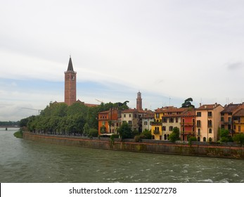 Verona, Italy - 6/8/2018: Colorful buildings on the Adige River, Verona, Italy with the Campanile of the church of Santa Anastasia visible over the green trees