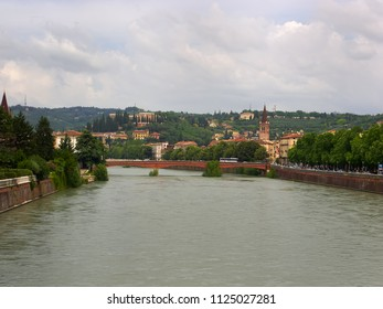 Verona, Italy - 6/8/2018: The River Adige flowing through Verona, Italy with Castel San Pietro in the distance on its hill overlooking the city