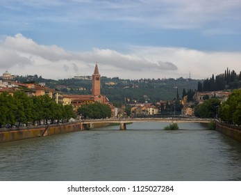 Verona, Italy - 6/8/2018: River Adige flowing through the city of Verona, Veneto, Italy with the church and campanile of Santa Anastasia and surrounding hills