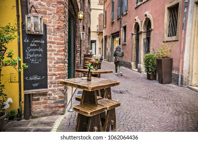 VERONA, ITALY - April 2018: Creative pub exterior on the historical street of Verona old town. Street bar with tables and chairs outside, Verona, Italy