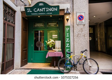 VERONA, ITALY - April 2018: Traditional Italian pizzeria exterior on the historical street of Verona old town. Street view of pizzeria door and decor elements, Verona, Italy