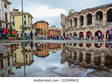 Verona / Italy — August 23, 2014: tourists walk on Piazza Bra near Arena di Verona on a rainy day. Verona Arena, a Roman amphitheater, is still in use; opera and concert performances  are given there