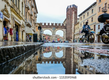 Verona / Italy — August 23, 2014: Portoni della Bra, a street arch gateway with the clock at the end of Corso Porta Nuova serves as the entrance to Piazza Bra, the largest square in the city