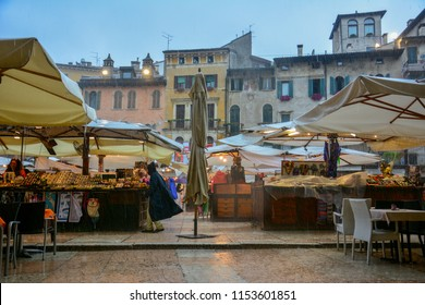 Verona / Italy — August 23, 2014: a heavy rain on the street market of Piazza delle Erbe in Verona, Italy. Once the town forum, this square in the center of the city is still used as a marketplace