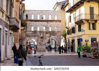 VERONA, ITALY - CIRCA OCT 2017: People walking near of Porta Borsari, ancient Roman gate in Verona city.