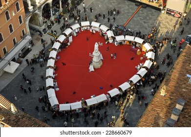 Verona, Italy - February 14, 2013: People in the Dante Square , where a large red heart has been placed. For the Valentine's day Verona is transformed into the city of love.