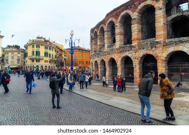 VERONA, ITALY, January 05 2018: Various people taking photos or just walking around and sightseeing Arena, a Roman Coloseum  in Verona, Italy.