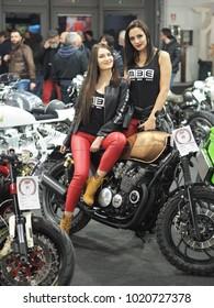 Verona, Italy - january 20, 2018: motor bike expo, two young hostess posing on motorbike..