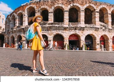 Verona, Italy - July 4, 2018 girl in a yellow dress with a backpack near the amphitheater. Verona amphitheater
