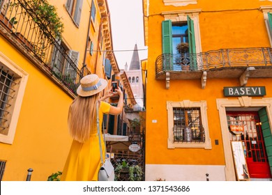 Verona, Italy - July 4, 2018 The girl in the dress is back to the camera and takes photos on the phone. cozy courtyard.